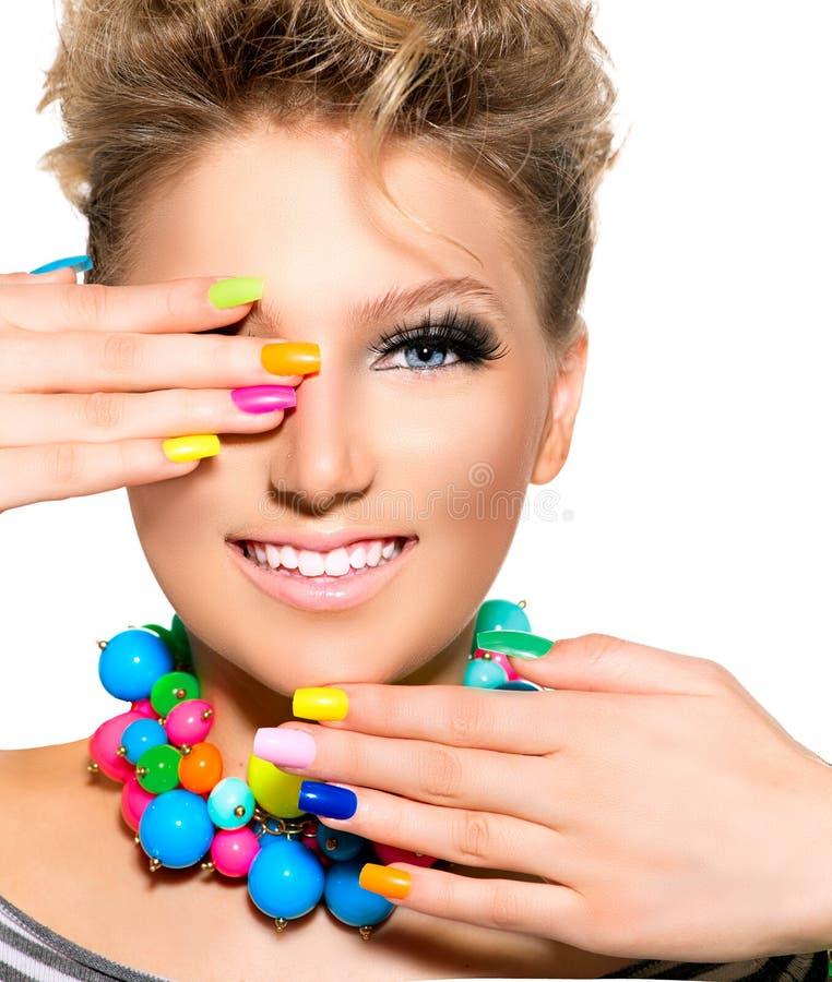 Skönhetflickan med färgrik makeup, spikar polermedel royaltyfri fotografi