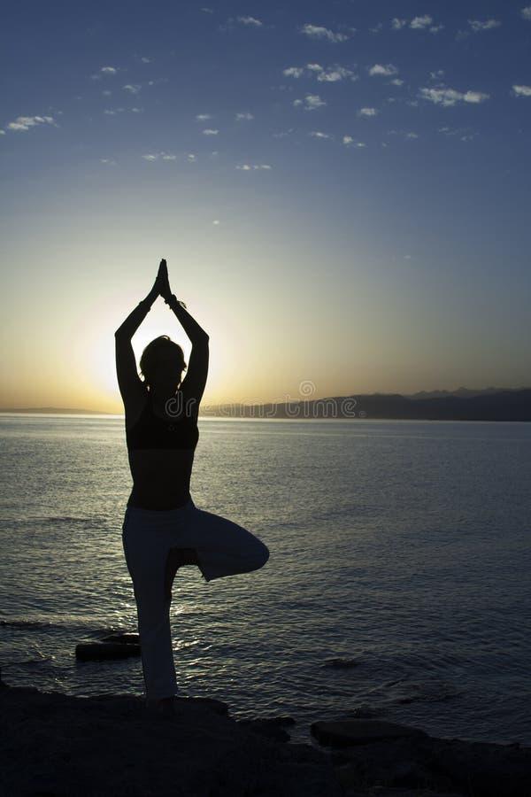 Skönhetflickan på stranden i yoga poserar, kopplar av konturn arkivbilder