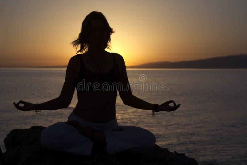 Skönhetflickan på stranden i yoga poserar, kopplar av konturn arkivfoton