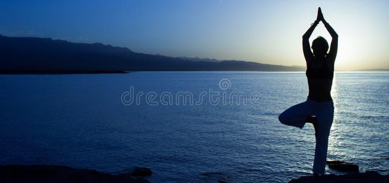 Skönhetflickan på stranden i yoga poserar, kopplar av konturn royaltyfri bild