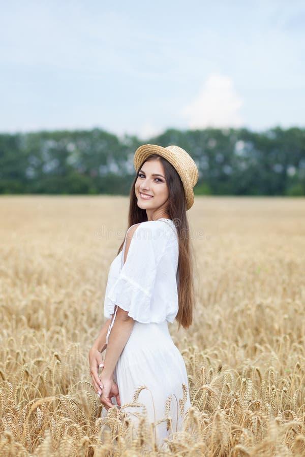 Skönhetflickastående i vetefält på solnedgången Attraktiv ung kvinna som ler och tycker om liv Härlig brunett med ett sunt royaltyfri bild