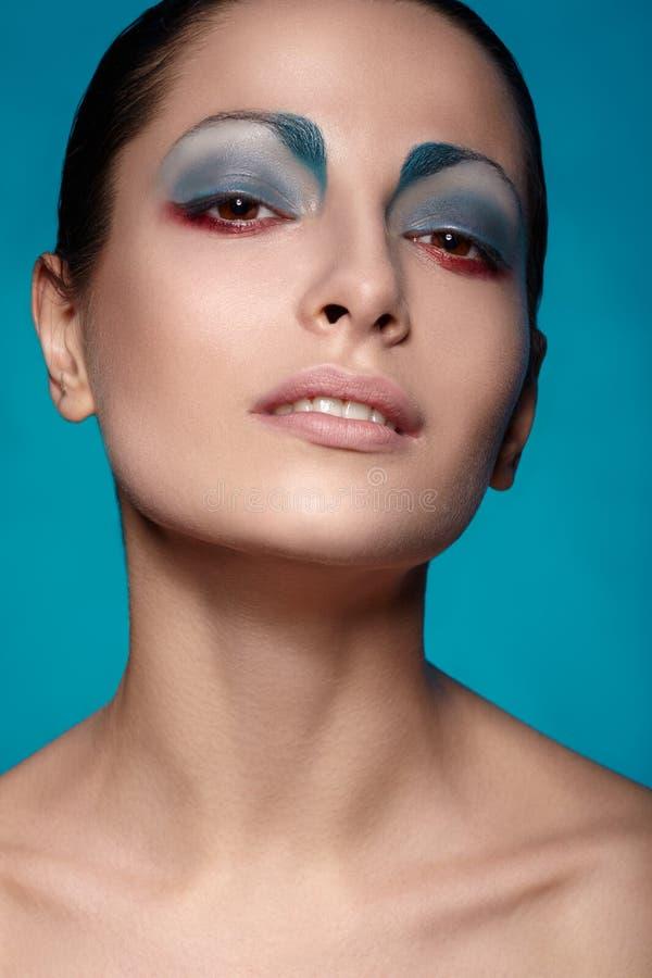Skönhetflickastående med färgrik makeup royaltyfri bild
