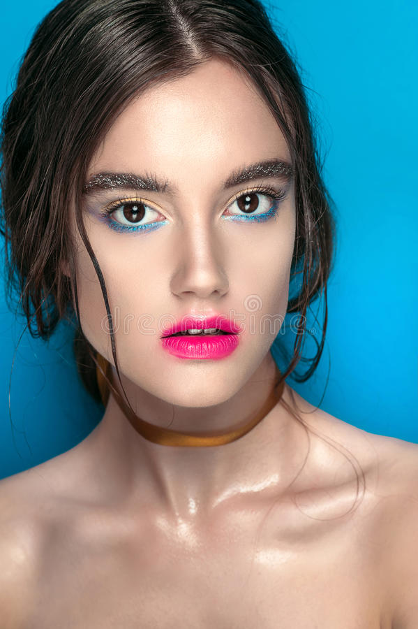 Skönhetflickastående med livlig makeup Dana kvinnaståendeslutet upp på blå bakgrund Ljust färgar Manikyrsmink rökigt arkivbilder
