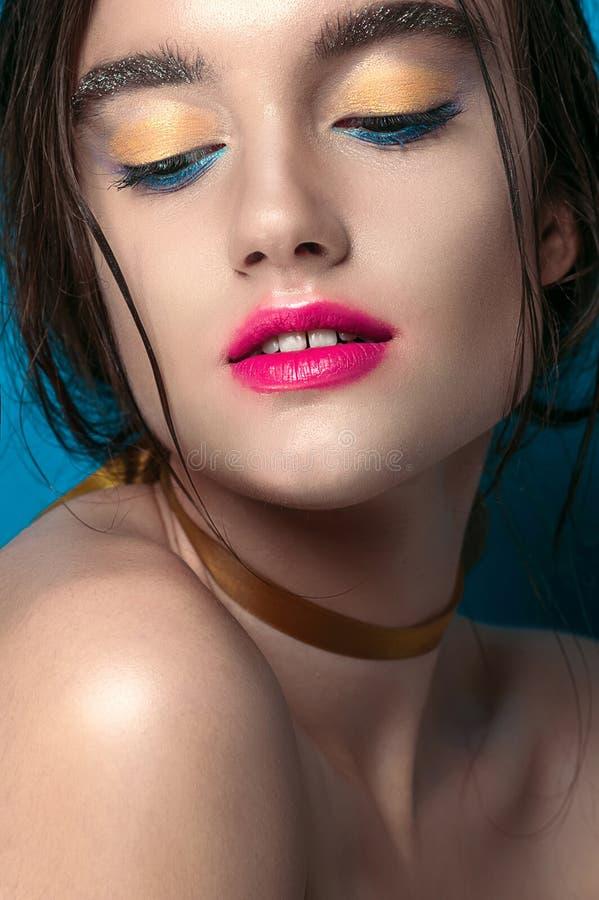 Skönhetflickastående med livlig makeup Dana kvinnaståendeslutet upp på blå bakgrund Ljust färgar Manikyrsmink rökigt royaltyfria foton