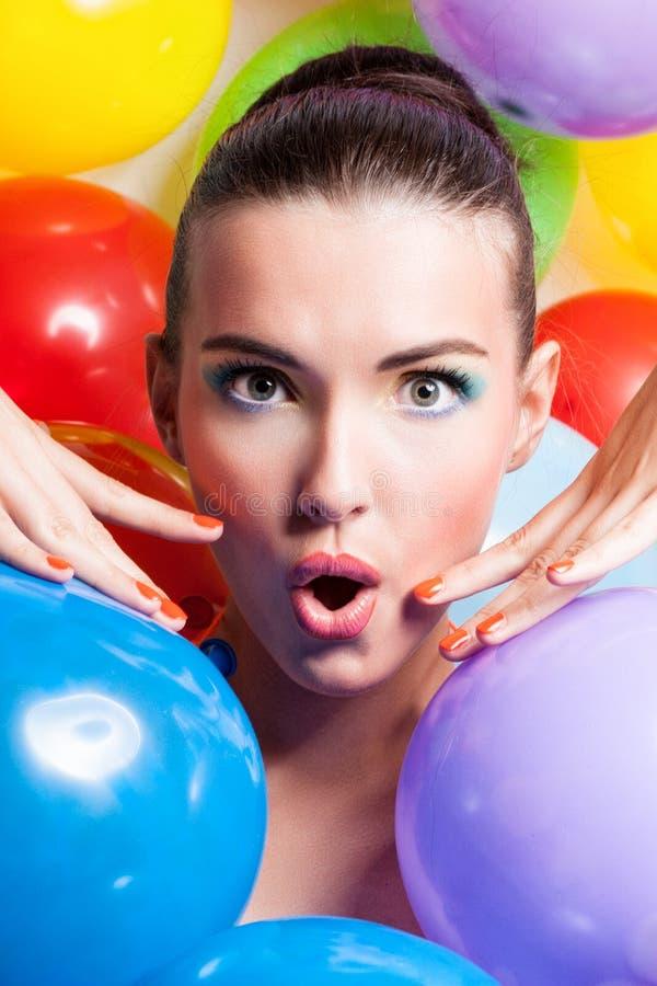 Skönhetflickaståenden med färgrik makeup, spikar polermedel och tillbehör Färgglad studio som skjutas av rolig kvinna colors livl royaltyfria foton