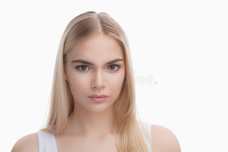 Skönhetframsida av den blonda tonåringflickan som isoleras på vit bakgrund arkivbild