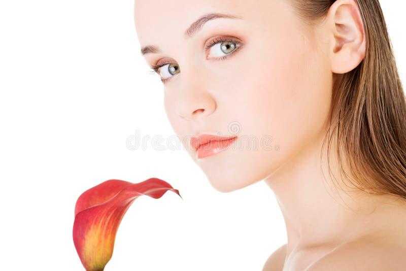 Skönhetframsida av den unga härliga kvinnan med blomman. arkivbild