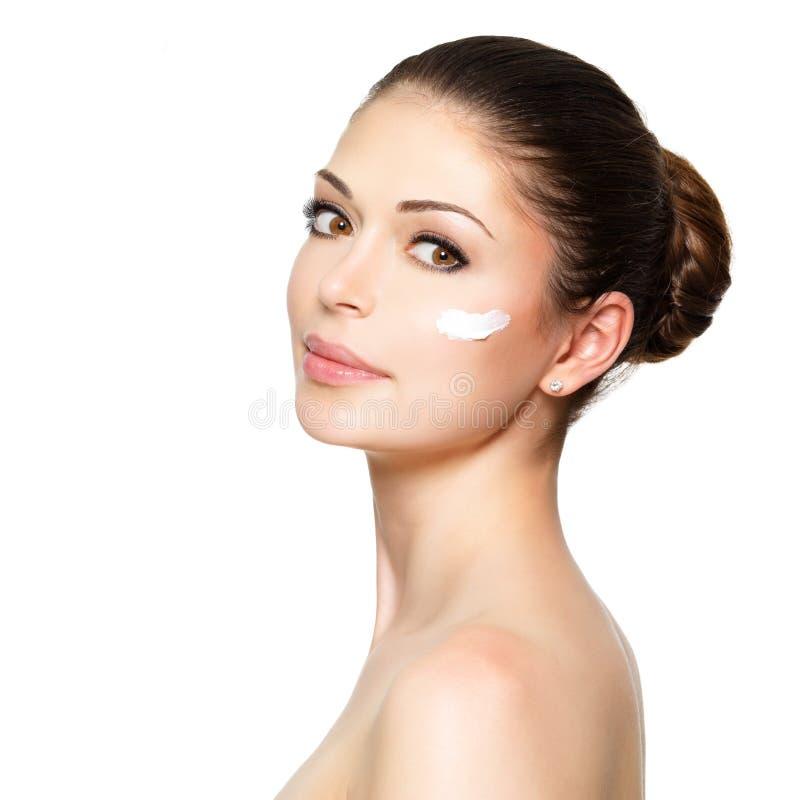 Skönhetframsida av kvinnan med skönhetsmedelkräm på framsida arkivfoto