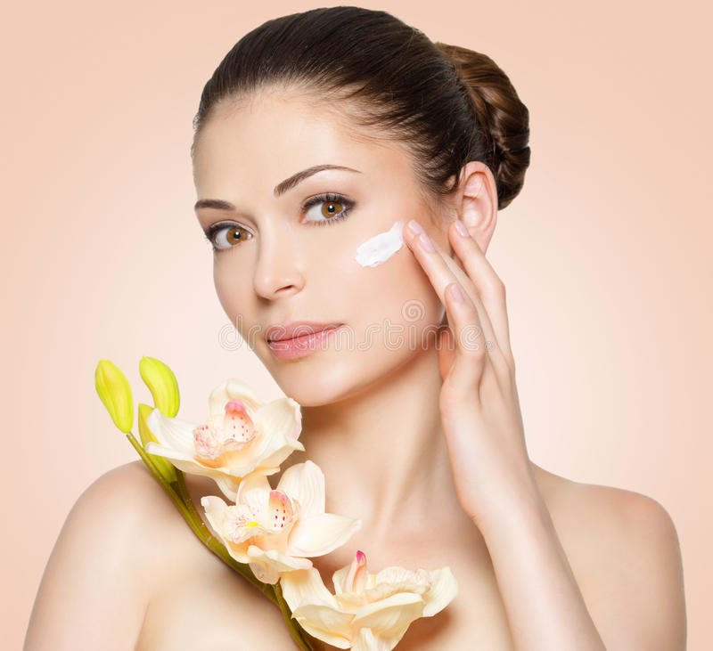 Skönhetframsida av kvinnan med skönhetsmedelkräm på framsida fotografering för bildbyråer