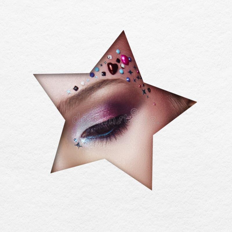 Skönhetframsidamakeup av en ung flicka i ett vitbokhål Kvinna med härlig makeup, ljusa ögon, lysande skugga i stjärnahål arkivbilder