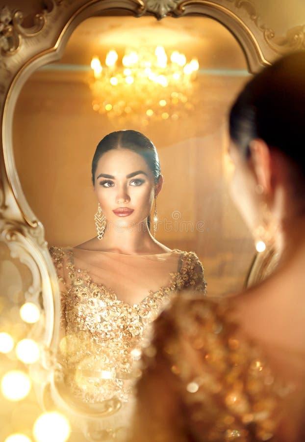 Skönhetglamourdam som ser i spegeln royaltyfria foton