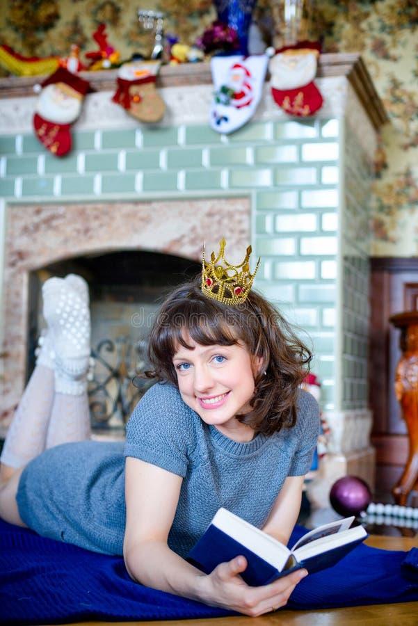 Skönhetglamourkvinna som firar jul som läser en bok som bär en klänning och en krona, festlig julbakgrund med jul arkivbild