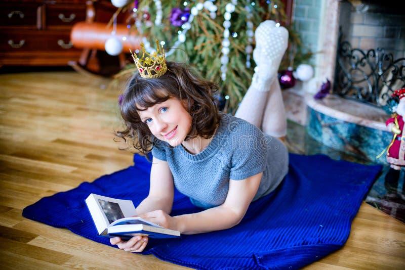 Skönhetglamourkvinna som firar jul som läser en bok som bär en klänning och en krona, festlig julbakgrund med jul arkivbilder
