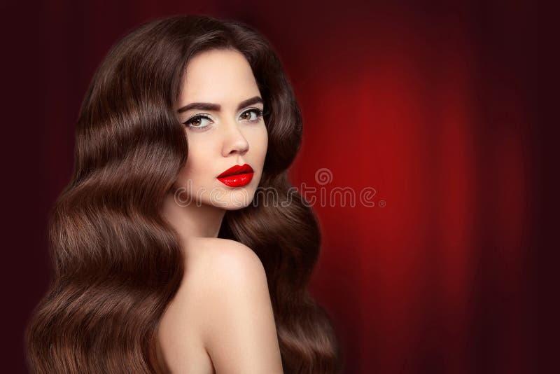 Skönhethår Brunettflickastående med röd kantmakeup och lon arkivbild