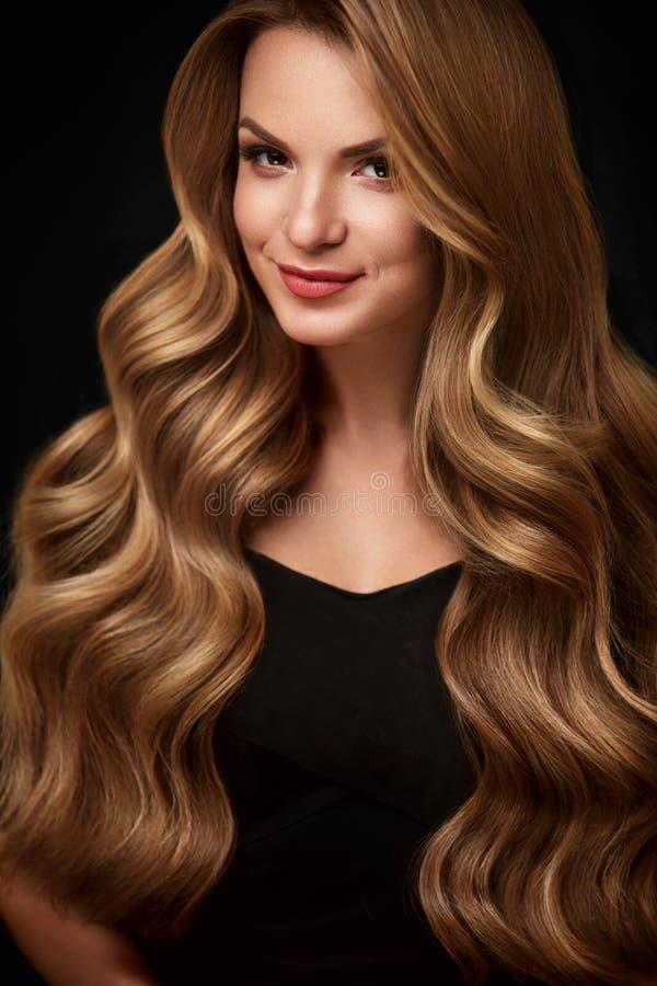 Skönhethår Härlig kvinna med lockigt långt blont hår royaltyfri bild