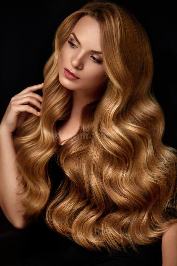 Skönhethår Härlig kvinna med lockigt långt blont hår royaltyfri foto