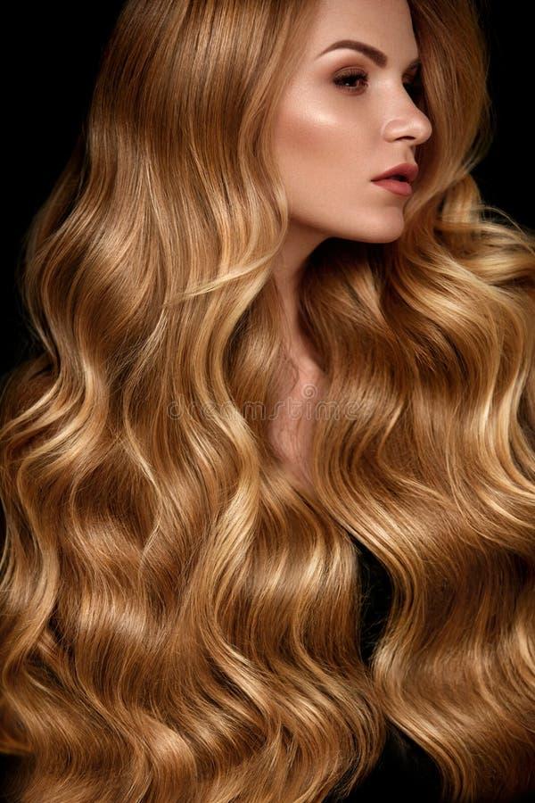 Skönhethår Härlig kvinna med lockigt långt blont hår arkivbilder