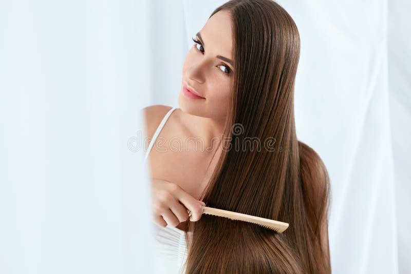Skönhethåromsorg Härlig kvinna som kammar långt naturligt hår arkivfoto