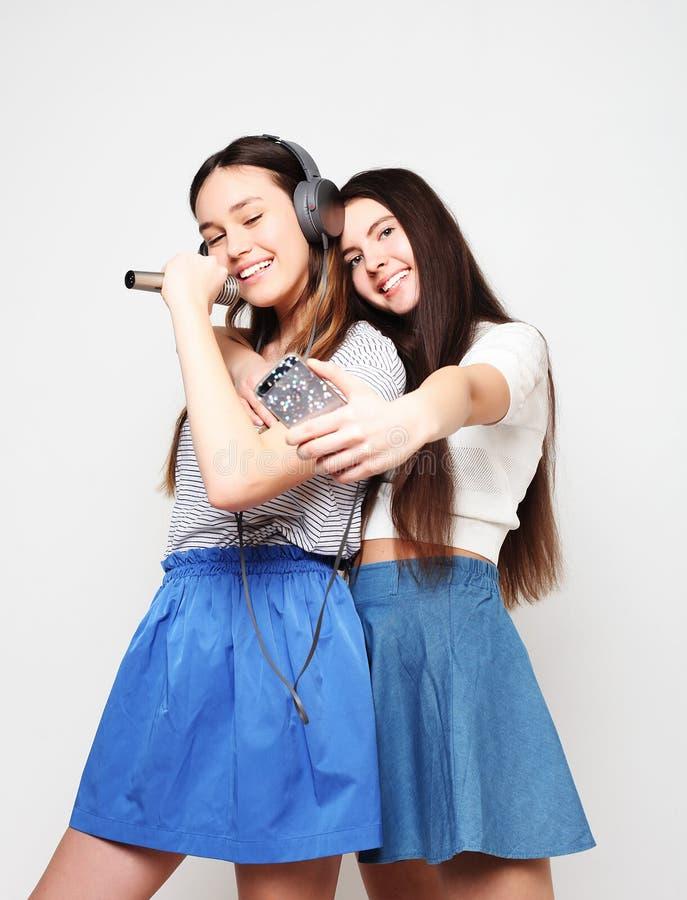 Skönhethipsterflickor med en mikrofon som sjunger och, tar bilden royaltyfria bilder