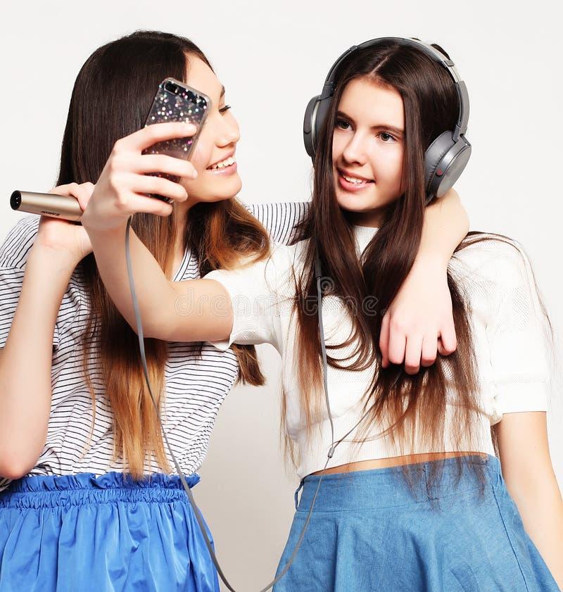 Skönhethipsterflickor med en mikrofon som sjunger och, tar bilden royaltyfri fotografi