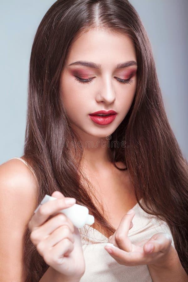 Skönhethudomsorg Härlig kvinna som applicerar kosmetisk framsidakräm royaltyfri foto