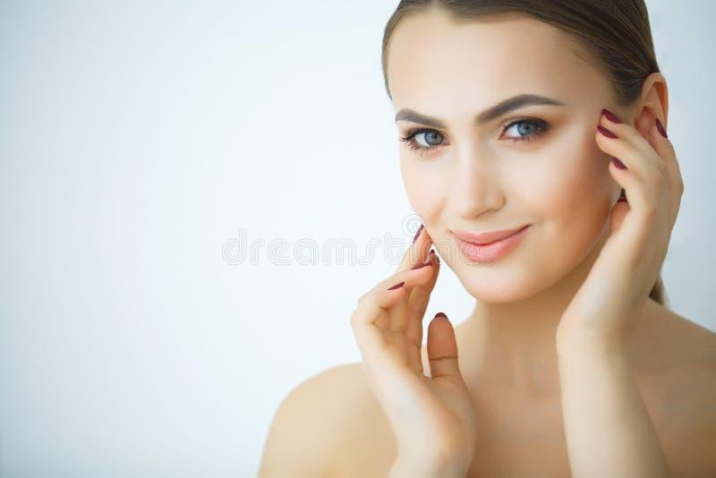 Skönhethudomsorg Härlig kvinna som applicerar kosmetisk framsidakräm royaltyfri bild
