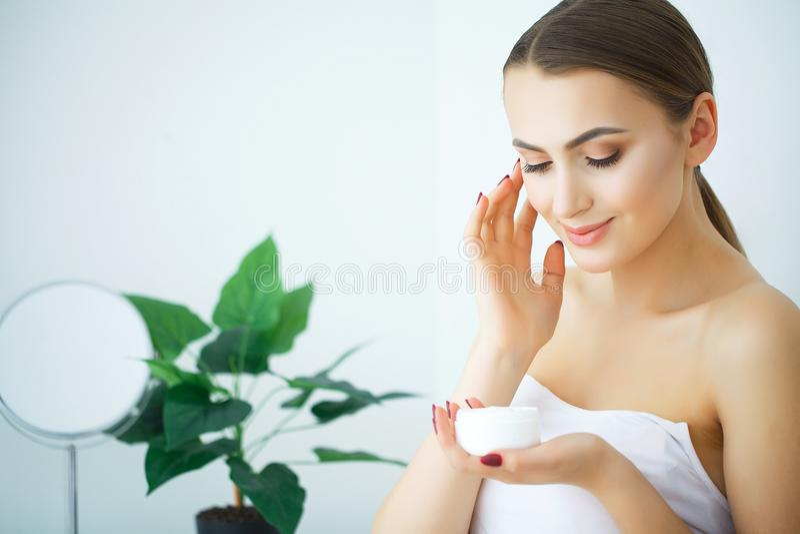 Skönhethudomsorg Härlig kvinna som applicerar kosmetisk framsidakräm fotografering för bildbyråer