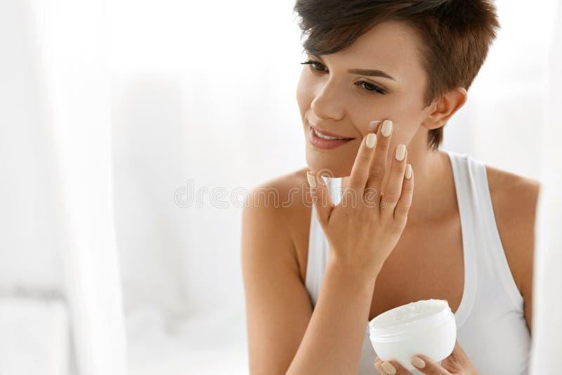 Skönhethudomsorg Härlig kvinna som applicerar kosmetisk framsidakräm royaltyfri fotografi
