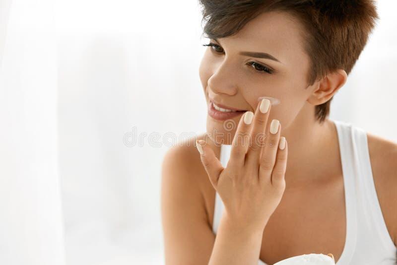 Skönhethudomsorg Härlig kvinna som applicerar kosmetisk framsidakräm arkivbild