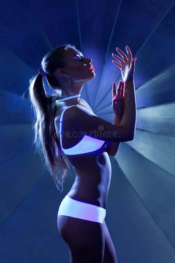 Skönhetkvinna i dans med det ultravioletta sminket arkivbilder