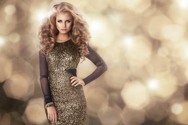 Skönhetkvinna i guld- klänning royaltyfria bilder