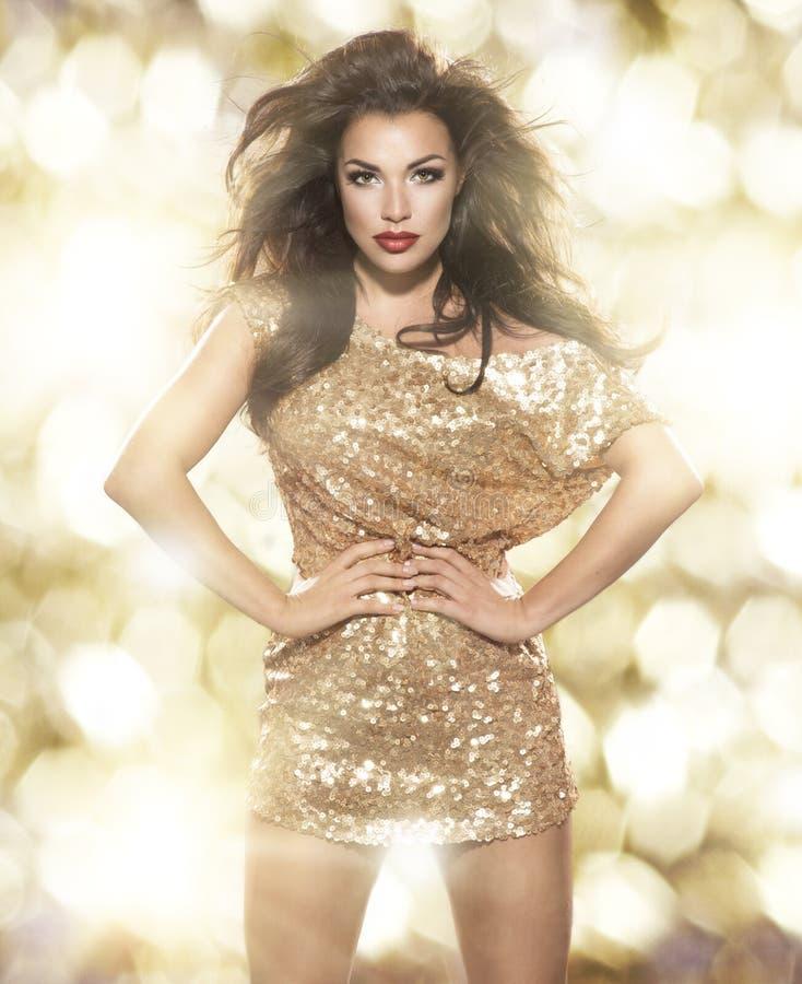 Skönhetkvinna i guld- klänning royaltyfri bild