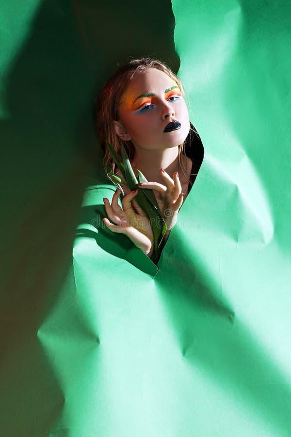 Skönhetkvinna med gruppblommor Yrkesmässig makeup och hairsty royaltyfria bilder