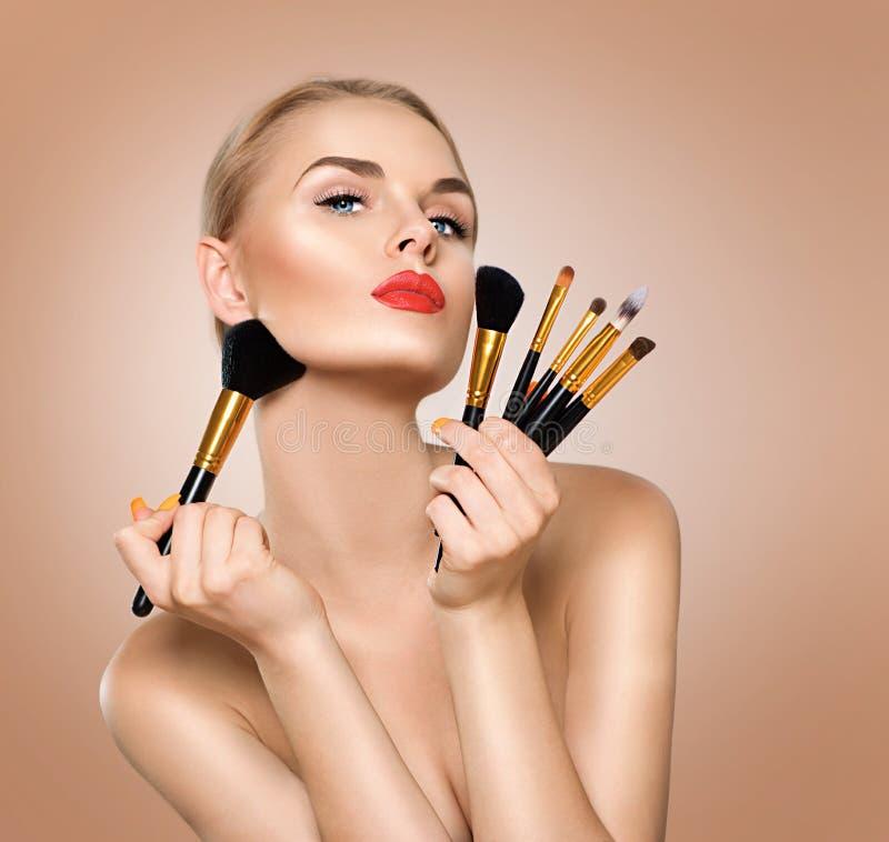 Skönhetkvinna med makeupborstar arkivfoto