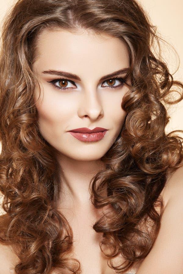 Skönhetkvinna med modesmink, långt lockigt hår royaltyfri bild