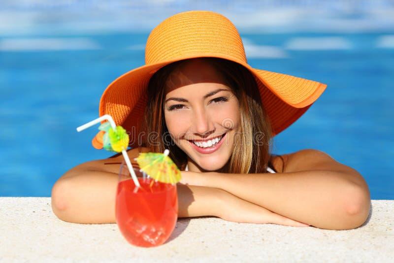 Skönhetkvinna med perfekt leende som tycker om i en simbassäng på semestrar arkivfoto