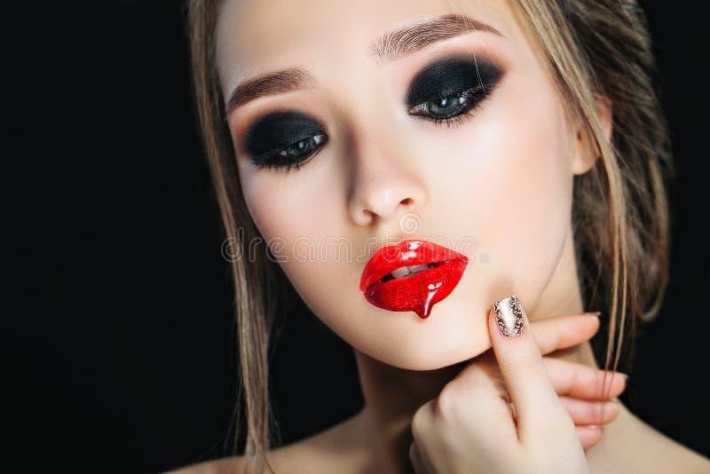 Skönhetkvinna med perfekt makeup och bruna hår Härligt yrkesmässigt feriesmink eyes rökigt Röda kanter spikar arkivfoton