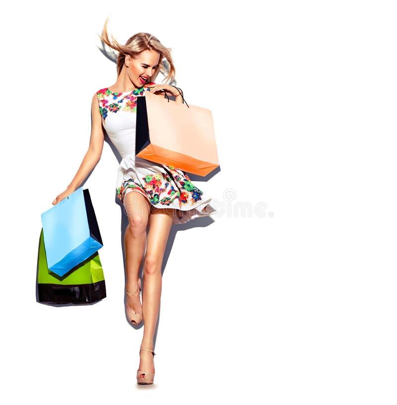 Skönhetkvinna med shoppingpåsar i kort vit klänning royaltyfri bild