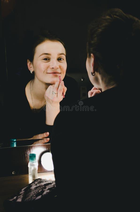 Skönhetkvinna som applicerar sminkkanter med blyertspennaläppstift Härlig flicka som ser i spegeln med kulor på dressingen i mörk royaltyfria foton