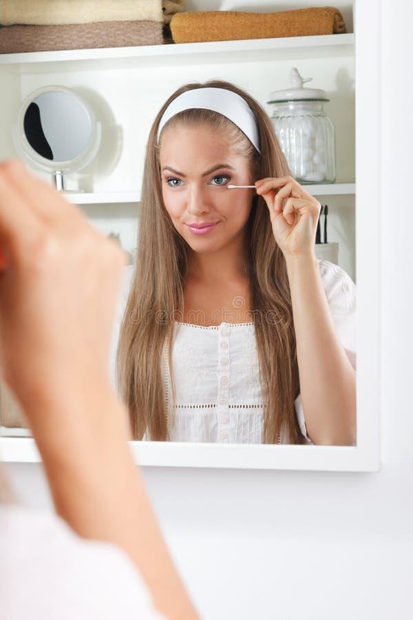 Skönhetkvinna som fixar hennes makeup i mirrowen royaltyfria foton