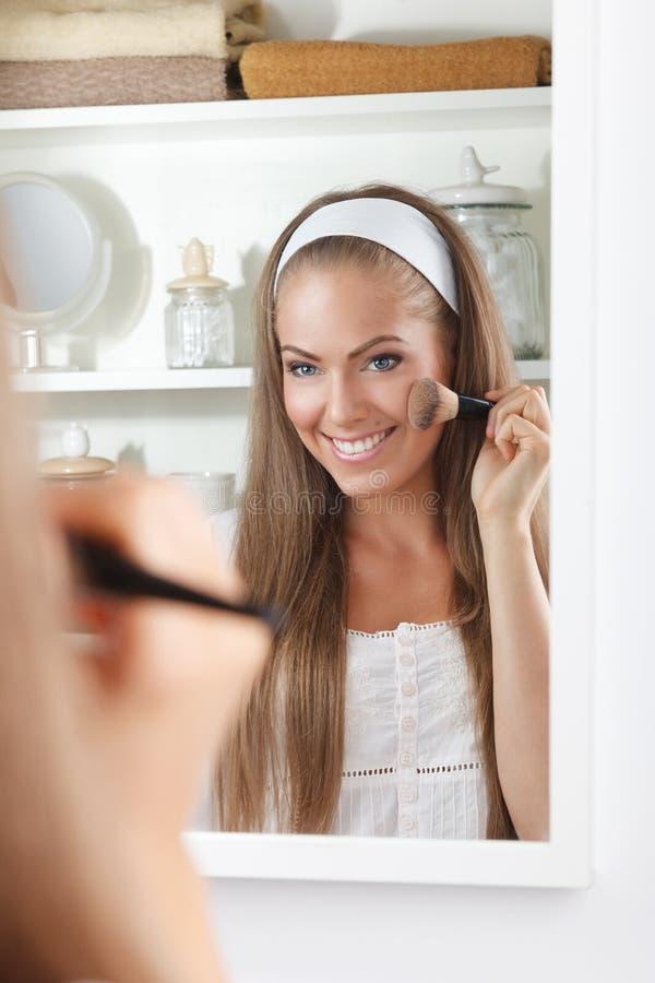 Skönhetkvinna som gör hennes makeup i spegeln royaltyfri fotografi