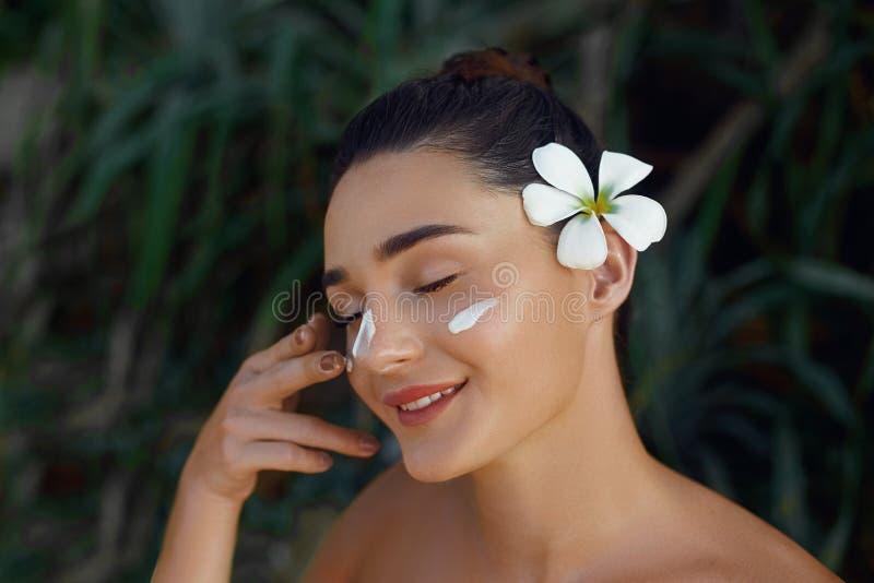 Skönhetkvinnabegrepp applicera genomskinlig fernissa f?r omsorgshud Ung modell med mjuk hud som rymmer kosmetisk kräm Stående av  arkivbild