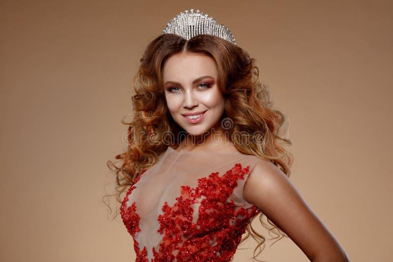 Skönhetkvinnaframsida med härliga sminkfärger Bilden av drottningen Rött hår, en krona på hans huvud, klar hud, härlig framsida royaltyfri foto