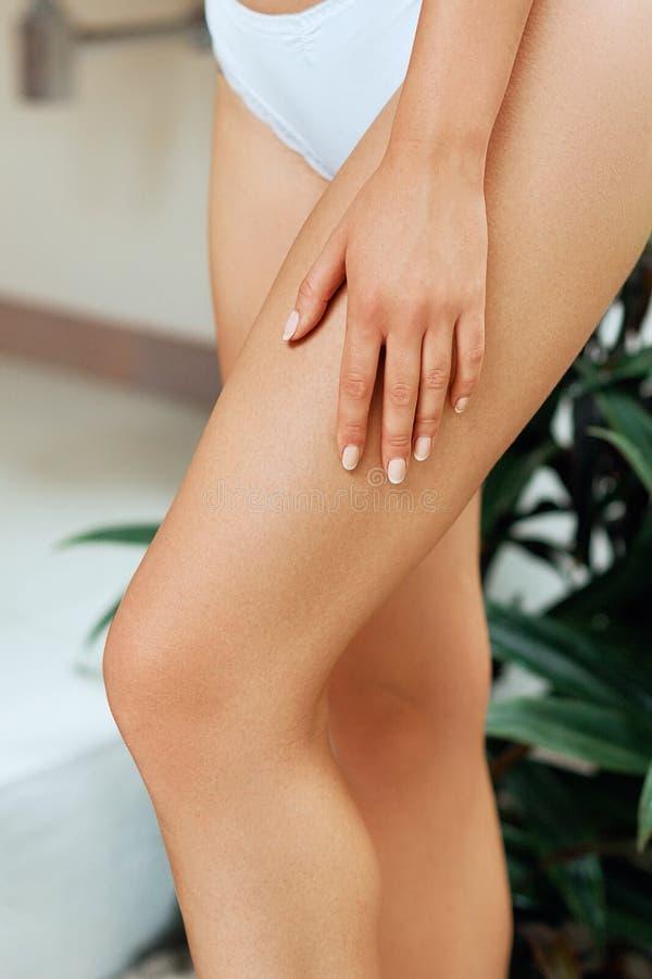 Skönhetkvinnan lägger benen på ryggen i badrum med slät mjuk hud efter hårborttagning Laser-epilation Sk?nhet- och kroppomsorgbeg arkivfoton