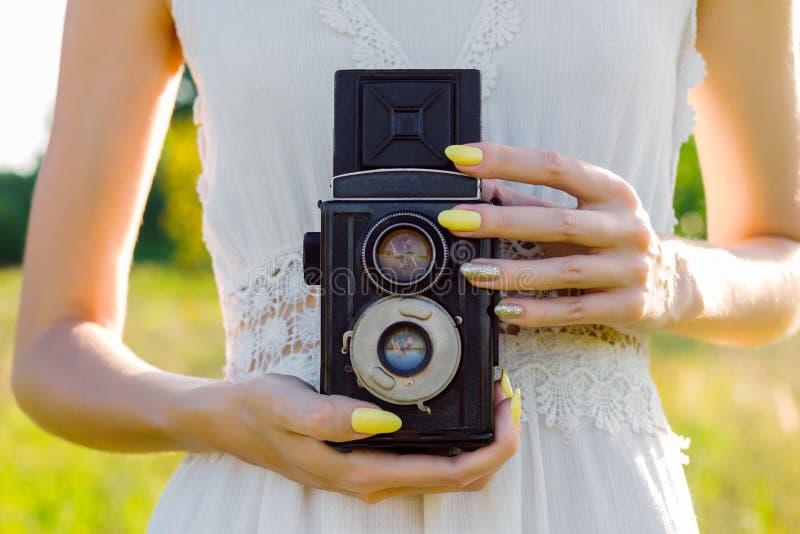 Skönhetkvinnan som tar fotoet på den utomhus- retro kameran parkerar in, i varm vårdag fotografering för bildbyråer