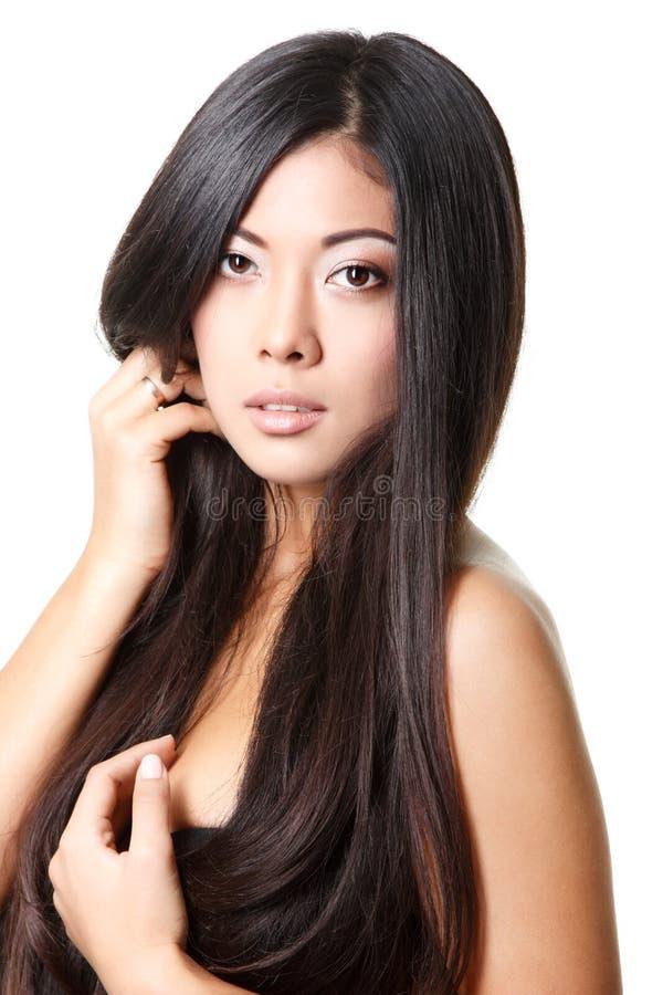 Skönhetkvinnastående av den unga härliga flickan med långa svarta mummel arkivfoto