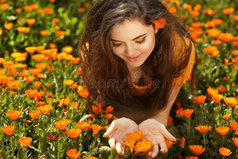 Skönhetkvinnastående med blommor. Fri lycklig brunett som tycker om royaltyfri foto