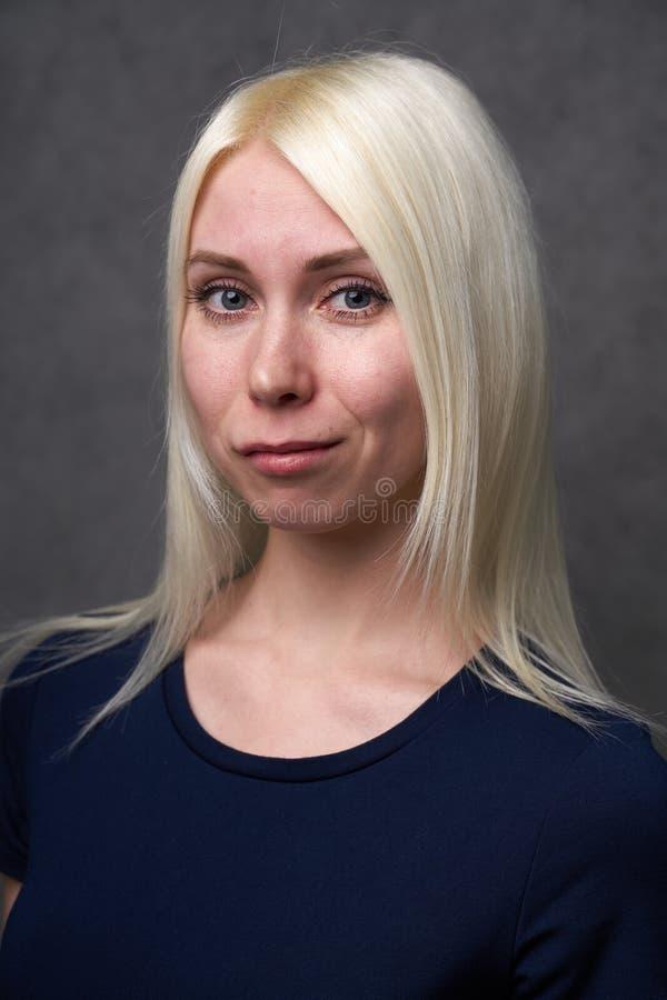 Skönhetkvinnlig som är blond i svart tillfällig kläder på grå bakgrund royaltyfri foto
