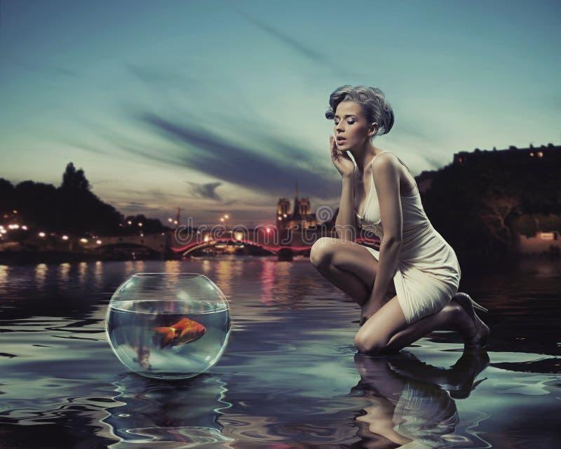 Skönhetlady med guldfisken royaltyfri bild