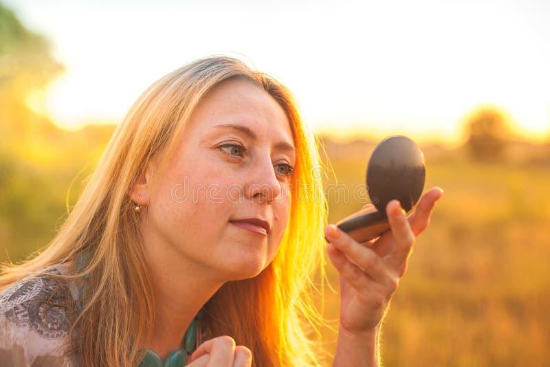 Skönhetmakeupbegrepp Den fundersamma kvinnan ser reflexionen i spegeln utomhus på solnedgången royaltyfria bilder